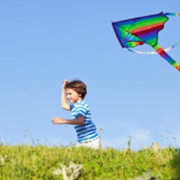 Child flying a kite on a sunny day