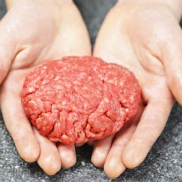 Hands holding raw meat